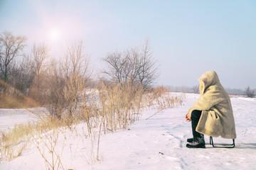Man sits in a fur coat on snowy plain