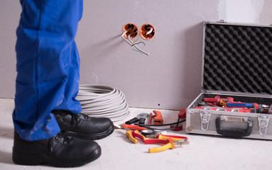 Elektriker installiert Steckdosen, verlegt Kabel