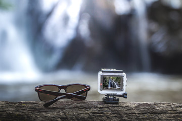 Sunglasses and action-cam on top of a brown tree with the waterfall behind.