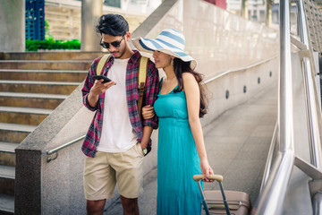 Young couple with travel bag using GPS navigation and map on smartphone. Couple, Love, Valentine, Travel technology, gadget and Summer concepts.