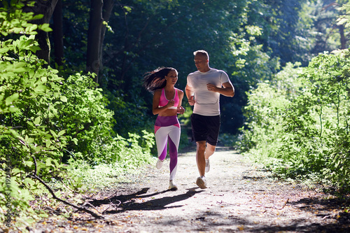 bcce8e7184c5 A man and a sportive woman Jogging in the woods and talking.