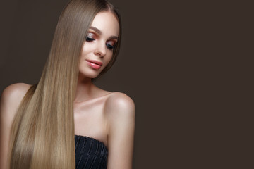 Wall Mural - Beautiful blond girl with a perfectly smooth hair, classic make-up. Beauty face. Picture taken in the studio .