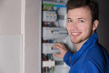 Freundlich schauender Elektriker arbeitet an einem Sicherungskasten, Elektroinstallation