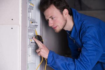 Elektriker arbeitet an einem Sicherungskasten