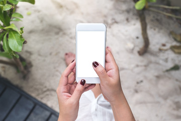 Mockup image of a woman's hands holding white mobile phone with blank black desktop screen with sand and beach background