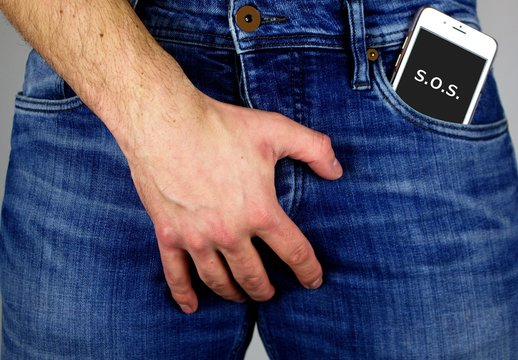 Young man with mobile phone in jeans pocket.Watch out for radiation.The cell phone radiation  harms male fertility.Be careful.
