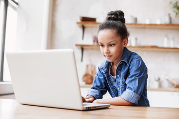 Cute little girl using laptop at home