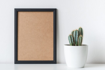 Modern room decoration. Cactus plant in white flower pot. Mock-up with a black frame.