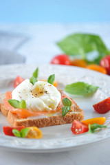 Toast with salted salmon and egg poached on a plate. The dish is decorated with multi-colored cherry tomatoes and basil leaves. Light background. Close-up. Vertical orientation of the frame.