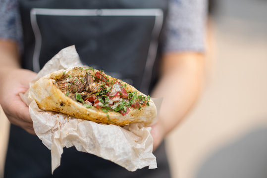 In the hands of the cook, falafel and fresh vegetables in pita bread