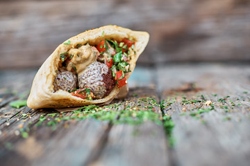 Falafel and fresh vegetables in pita bread on wooden table. Healthy lifestyle. Selective focus.