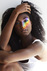 Rainbow light on beautiful young woman, portrait