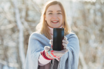 Young caucasian attractive blonde girl in pink sweater and knitted scarf holds smartphone in winter park outdoor