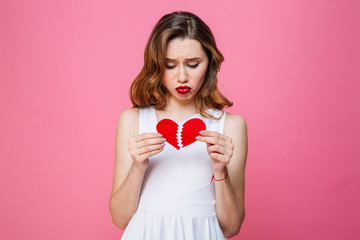 Young sad woman holding broken heart. Looking aside.