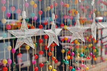 Garland in the form of large transparent stars hanging on a background of colorful beads on ropes