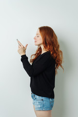 Young redhead woman reading a text message