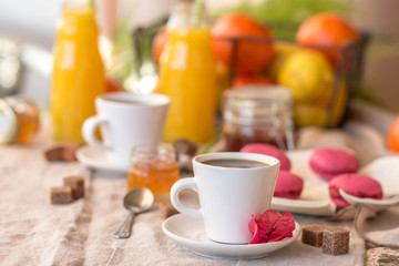 Breakfast with coffee cups, orange juice, makaron the outdoor terrace