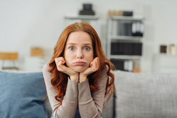 Young upset woman sitting on sofa at home
