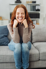 Friendly young redhead woman sitting on a sofa