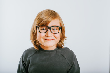 Studio shot of cute little boy wearing eyeglasses
