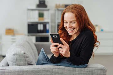 Young cheerful woman using mobile phone on sofa