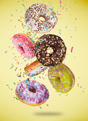 Tasty doughnuts in motion falling on pastel yellow background.
