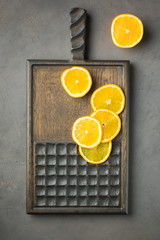 Wooden textured cutting board made of oak on a gray concrete background with pieces of orange. Background pattern with high resolution. Top view Copy space