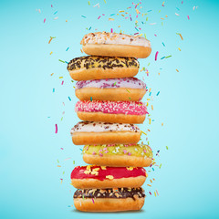 Tasty doughnuts on pastel blue background.