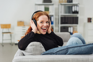 Cute vivacious young woman listening to music