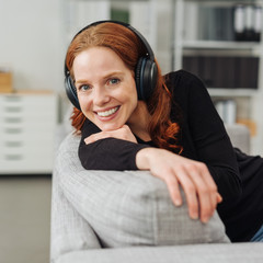 Smiling woman listening to music on headphones