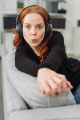 Young woman whistling as she listens to music