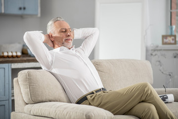 Time to dream. Positive delighted bearded man crossing legs while sitting on the sofa, stretching arms