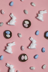 Easter background with easter eggs and easter bunnies on a pink background