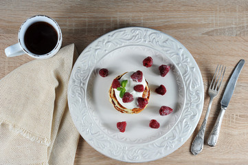 Pancakes on a white plate. On top of the pancakes are sour cream and decorated with raspberries and mint leaves. In the frame cutlery, napkin, a cup of coffee. View from above.