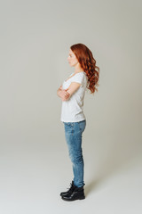 Young casual woman in jeans standing sideways