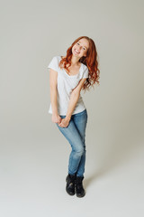 Cute happy young redhead woman in jeans