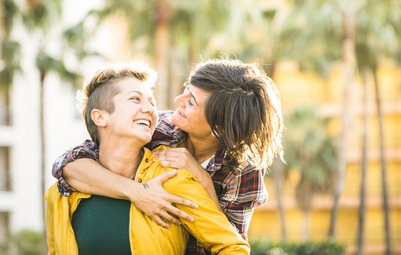 Happy playful girlfriends in love sharing time together at travel trip on piggyback hug - Women friendship concept with girls couple having fun on fashion clothes outdoors - Bright warm sunset filter