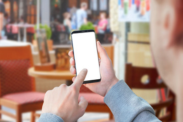 Man use mobile phone with isolated screen for mockup in coffee shop. Modern smart phone with round edges.