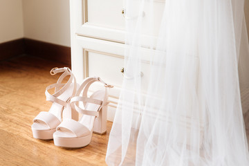 Bridal pink shoes standing in front of the nightstand. Bridal veil falling down from the nightstand.