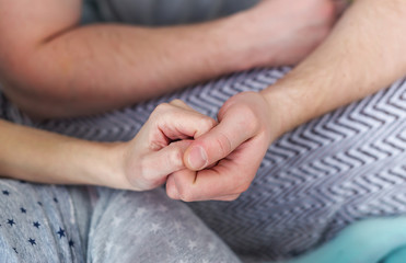Close-up photo of a loving couple holding hands.