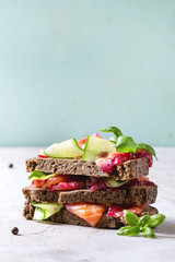 Sliced beetroot marinated salmon sandwiches with rye bread, cucumber, basil and lemon served in stack on wooden cutting board over grey blue texture background. Close, up, space