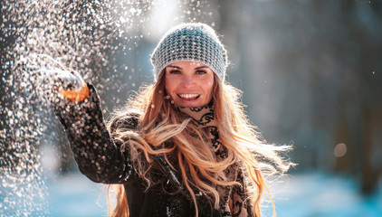 Smiling young woman throwing snow in the air looking at camera