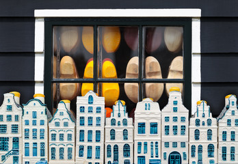 Dutch clogs behind a window and souvenir Amsterdam houses