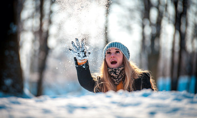 Young woman throwing snowball at sunny day in winter park