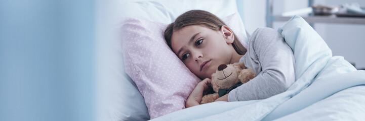 Sick girl hugging plush toy