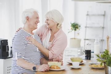 Smiling senior woman hugging husband