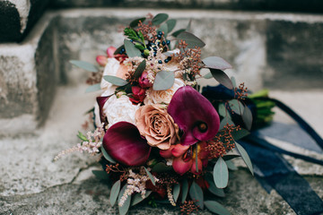 beautiful red wedding bouquet of bride in style rustic on a stone background