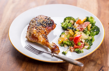 Grilled chicken leg seasoned with soy sauce and coated in a crispy crust of sesame seeds and apricot marmalade served with broccoli salad, overhead view on a plate