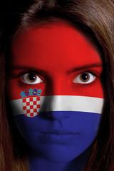 Junge Frau mit kroatischer Fahne im Gesicht
