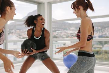 Women enjoying exercising with medicine ball at gym